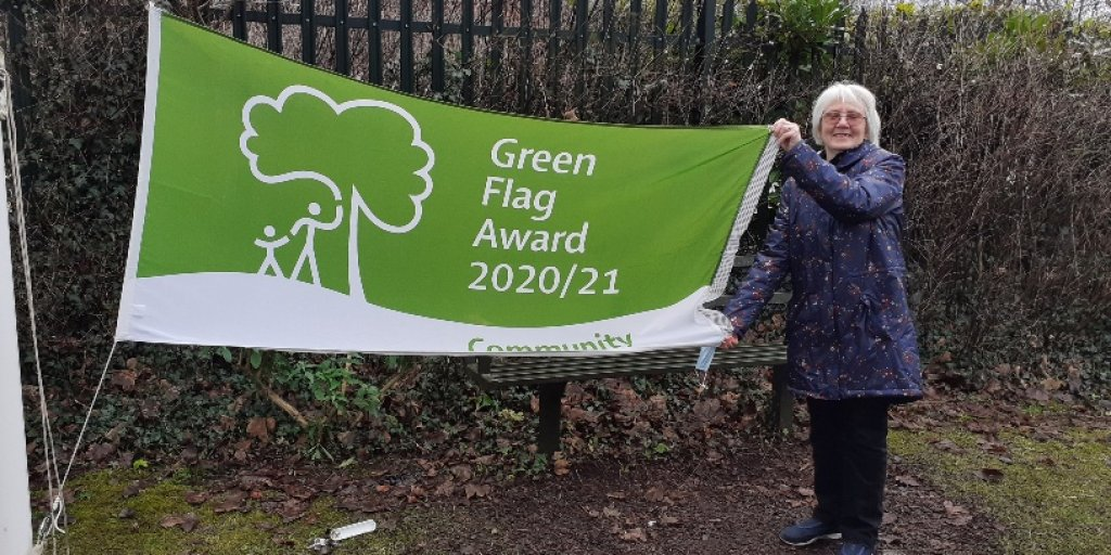 Photo shows Pat Cook with the Forest Road Greenbelt's Green Flag Community Award.